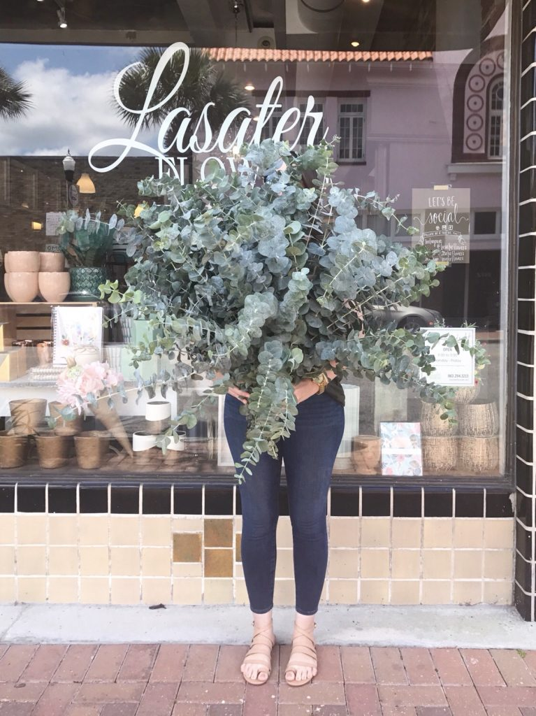 Florist standing in front of a flower shop holding huge bundle of jumbo spiral eucalyptus