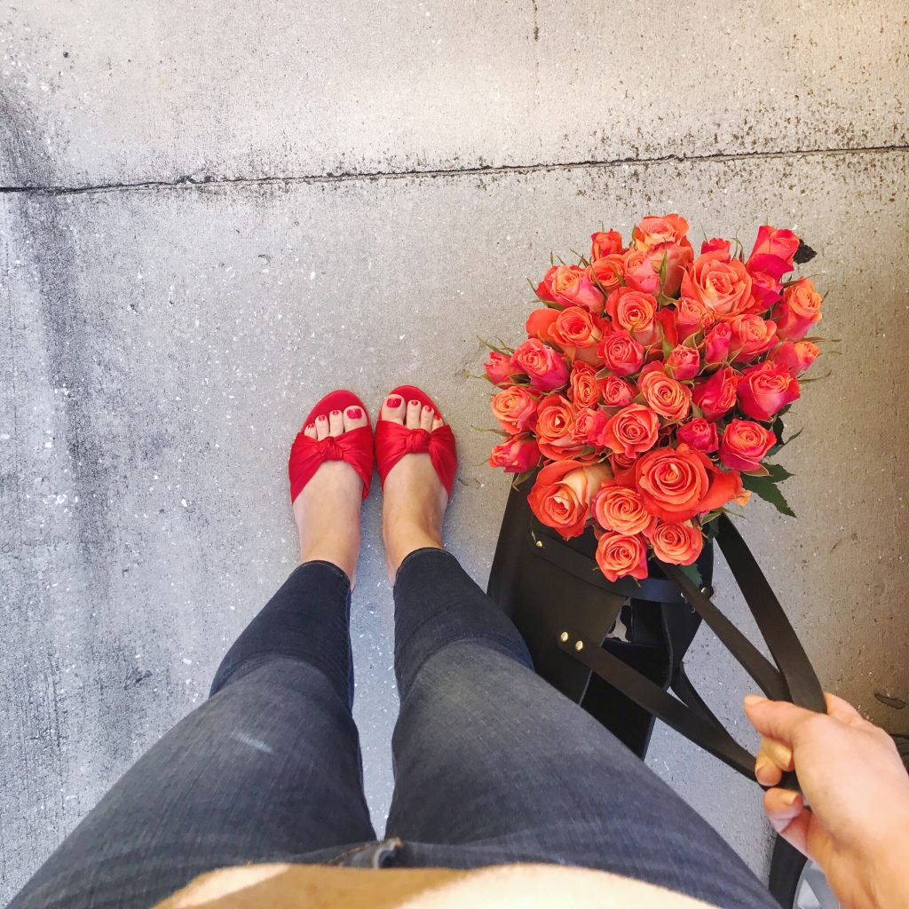 LOFT red satin knot slide sandals with tee and dark skinny jeans, orange spray roses in leather tote bag