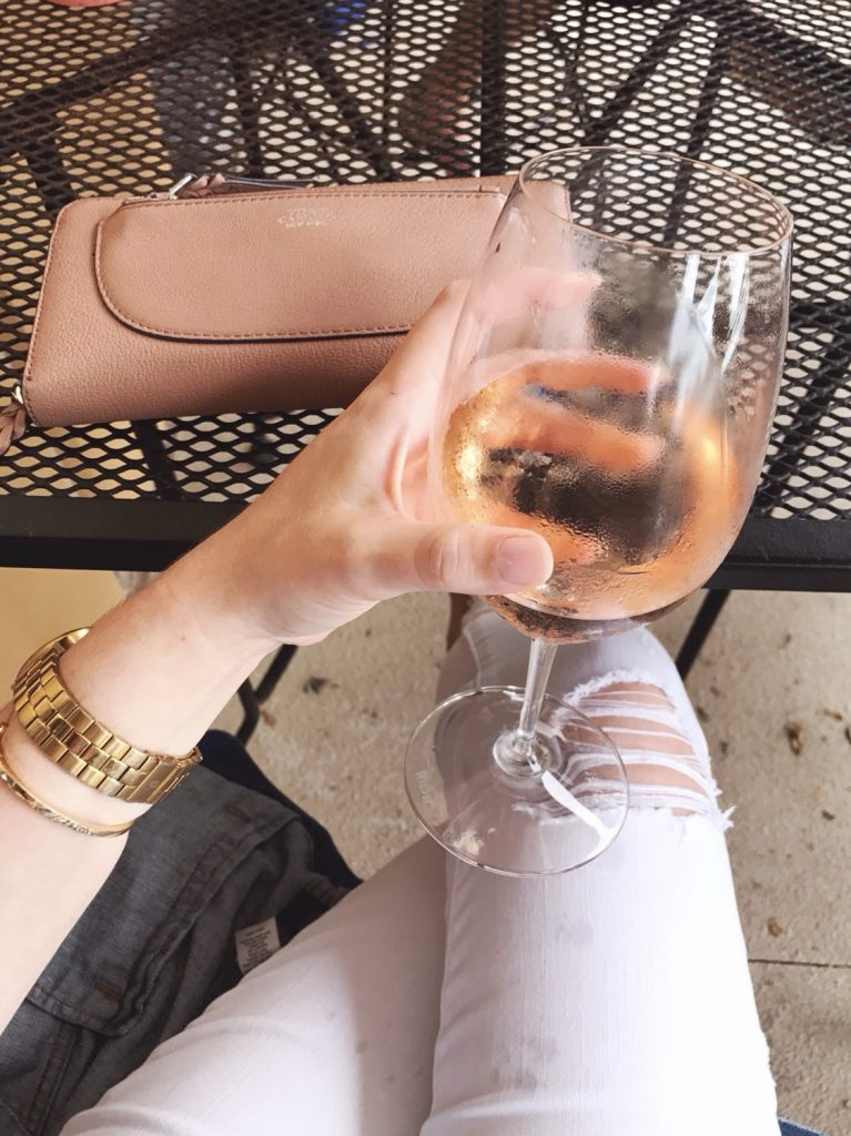 Glass of Rose with distressed summer white jeans and gold accessories