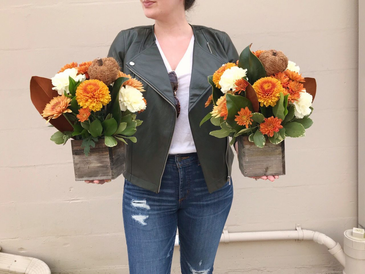 Woman wearing olive green faux leather jacket and distressed skinny jeans holding two fall floral arrangements with orange mums, cream carnations, magnolia and sisal pumpkins
