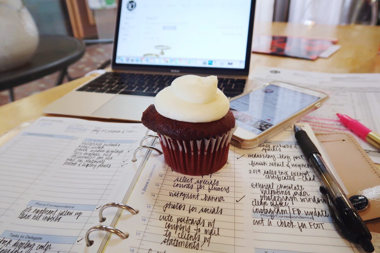 Red velvet cupcake sitting on a desk with Filofax personal organizer, Macbook, iPhone and assorted pens.
