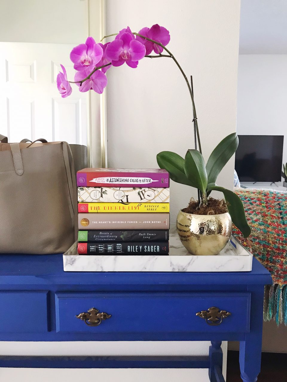 Stack of unread Book of the Month books on a blue console table, between a purple potted orchid plant and a taupe leather Cuyana structured tote bag.