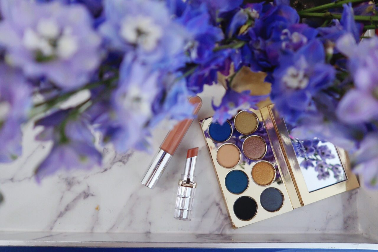 Violette Fr x Estee Lauder La Dangereuse 'Blue Dahlia' eye shadow palette on a marble tray beside of vase of fresh blue delphinium flowers, L'Oreal Colour Riche lipstick, and Becca lip gloss.