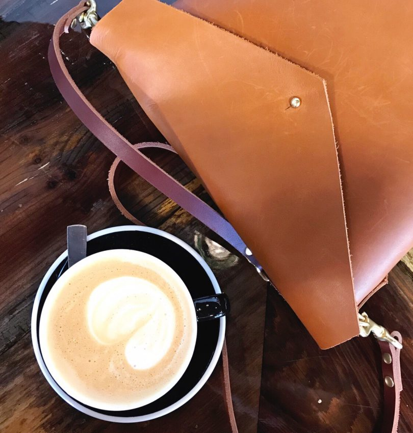 Cappucino on a coffee shop counter next to a leather satchel crossbody bag