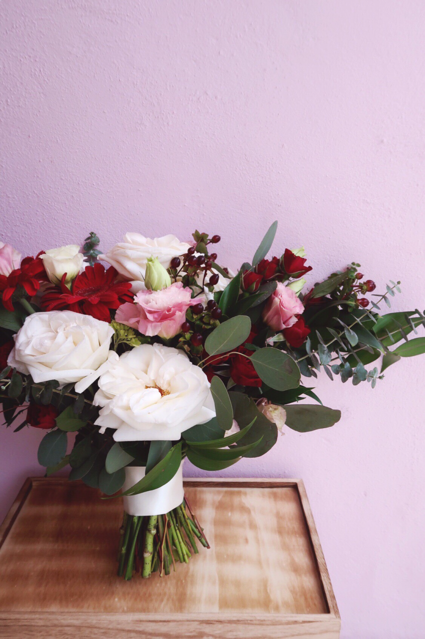 Hand-tied bridal bouquet with white garden roses, pink lisianthis, and burgundy gerbera daisies, hypericum berries and spray roses.
