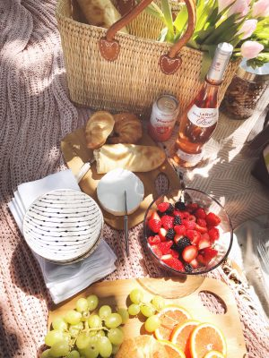 Outdoor picnic setup on a blanket with a woven market tote, bottle of Rose, fresh fruit and cheese and bread.