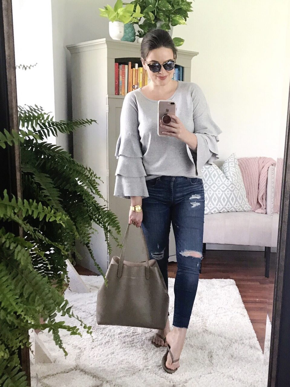 Style blogger wearing gray ruffle-sleeve sweater with distressed LOFT skinny jeans and TKEES gray leather flip flops, carrying Cuyana structured leather tote bag.
