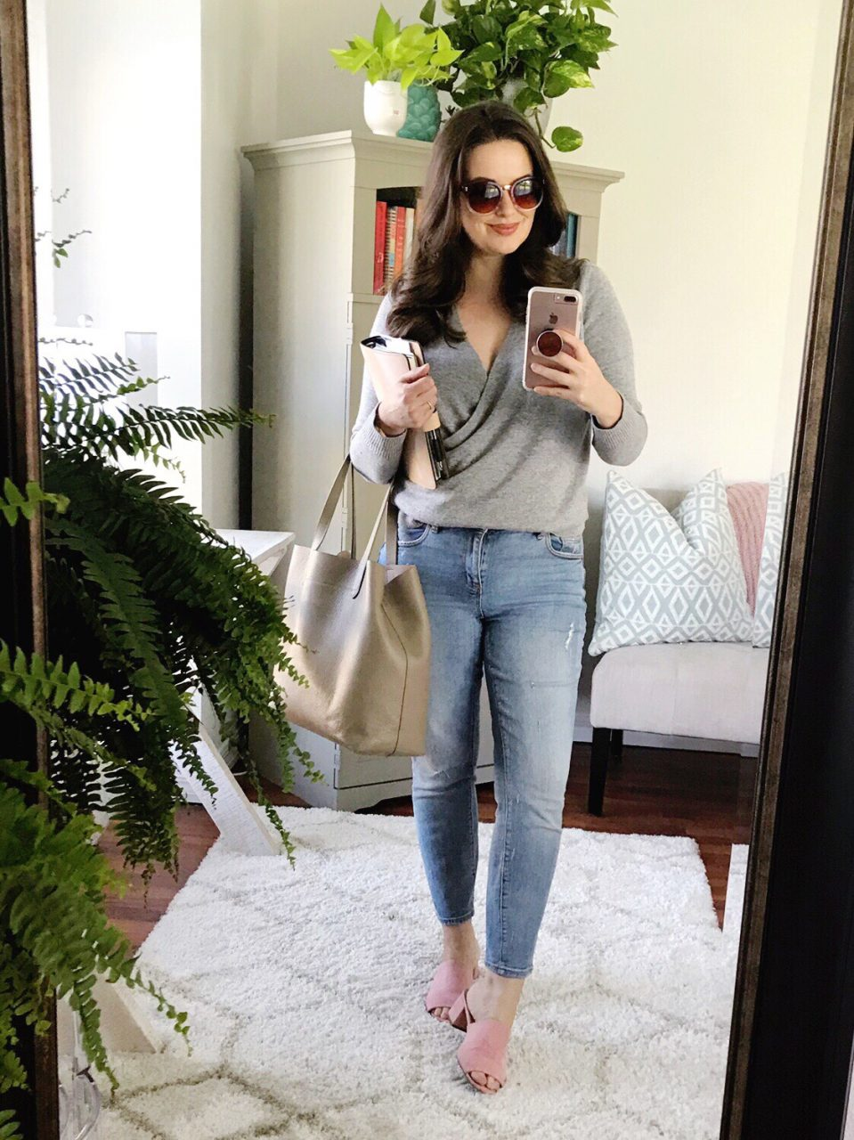 Style blogger wearing gray LOFT wrap sweater with LOFT boyfriend jeans and pink suede mules, carrying Cuyana structured leather tote bag.