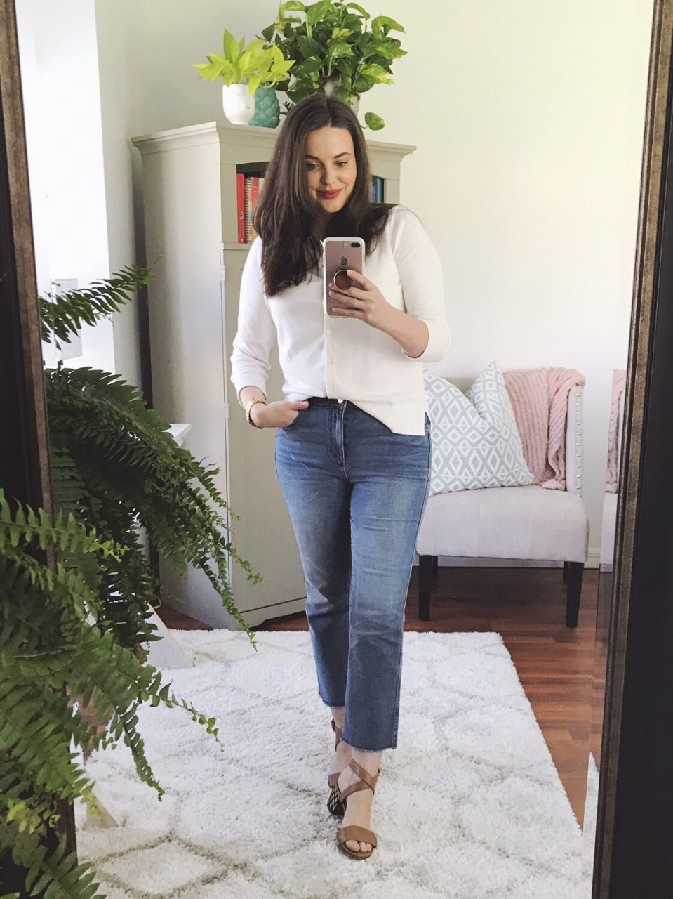 Style blogger wearing cream LOFT cardigan buttoned up and tucked into wide leg cropped jeans.