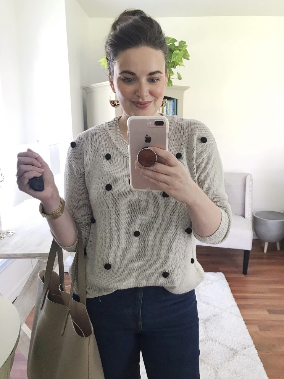 Style blogger wearing a gray sweater accented with black pom-poms and Everlane authentic stretch hi-rise skinny jeans in dark blue.