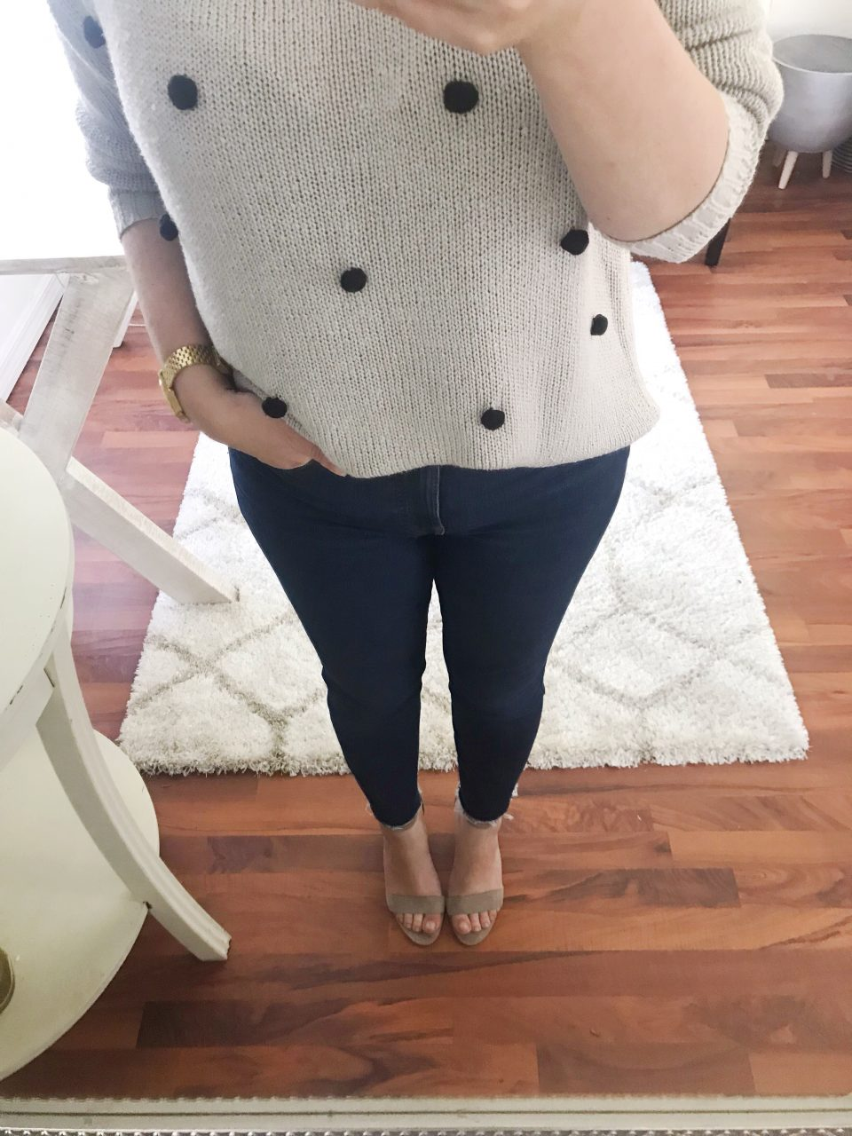 Style blogger wearing a gray sweater accented with black pom-poms and Everlane authentic stretch hi-rise skinny jeans in dark blue with taupe suede Vince Camuto block heel sandals.