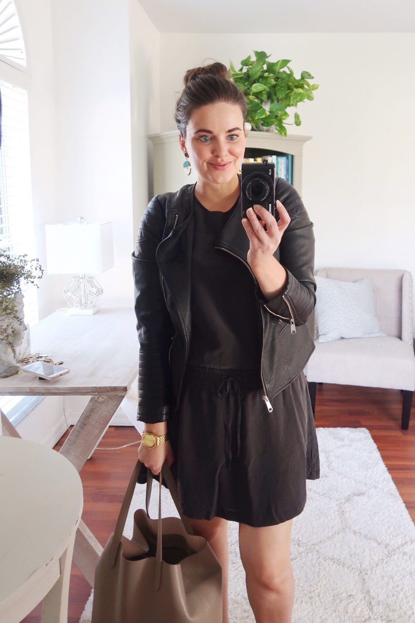 Style blogger wearing vegan leather black motorcycle jacket over a black silk tank dress with blue and gold statement earrings.