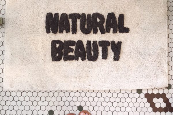 Bathmat that says 'Natural Beauty' on a vintage tile floor