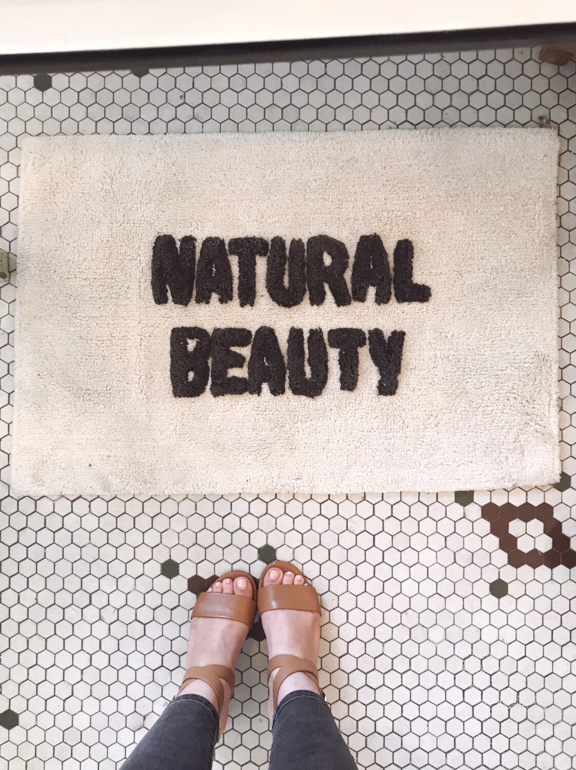 Bathmat that says 'Natural Beauty' on a vintage tile floor