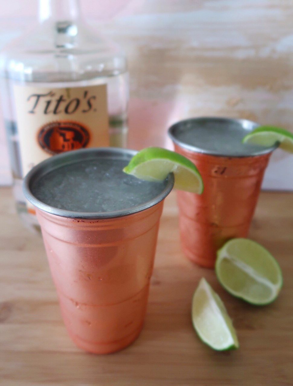 Frozen Moscow Mules with fresh lime wedges and Tito's vodka on wood cutting board