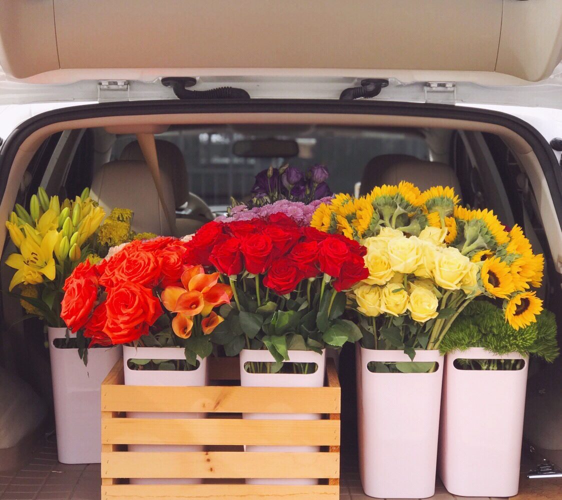 Nissan Murano cargo area filled with buckets of colorful fresh flowers, including red and orange roses, yellow roses and lilies, sunflowers, and mango calla lilies